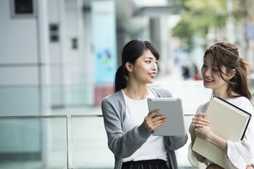 タブレットを眺めながら話し合う女性たち