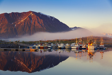 Fishing boats in harbor at midnight sun and fog in Northern Norway, Lofoten Island, Norway