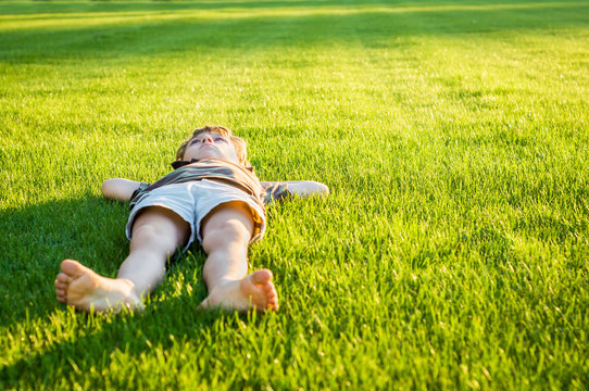 The boy lies on a well-groomed lawn illuminated by the sun's rays