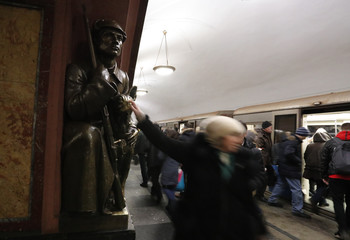 A woman touches a sculpture of a dog for good luck at Ploshchad Revolyutsii metro station in Moscow