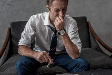 businessman with drug addiction sniffing cocaine while sitting on couch