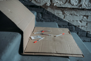 close-up shot of heroin syringes on cardboard and on stairs