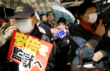 Protesters attend a rally denouncing Japanese Prime Minister Shinzo Abe and Finance Minister Taro Aso over a suspected cover-up of a cronyism scandal, in Tokyo