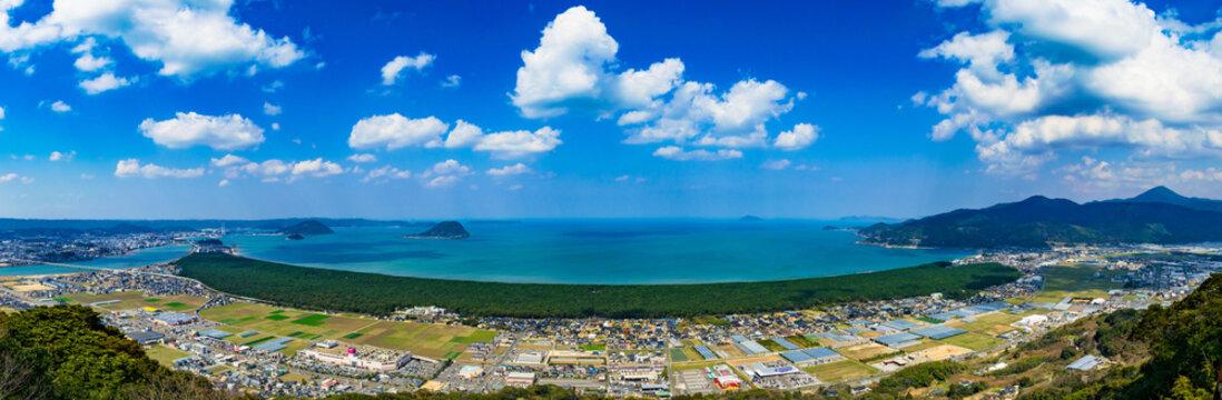 鏡山展望台から見る「虹の松原」虹の弧のように連なる緑の松原と唐津湾の青い海が美しい絶景 松原の西端には唐津城が見える