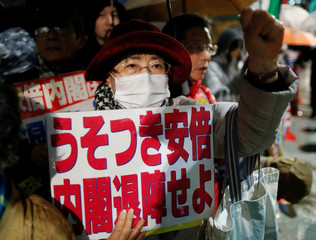 Protesters shout slogans and hold placards during a rally denouncing Japanese Prime Minister Shinzo Abe and Finance Minister Taro Aso over a suspected cover-up of a cronyism scandal, in Tokyo