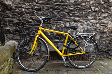 modern yellow bicycle near old stone wall in Ghent, Belgium