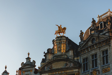 low angle view of statues on antique buildings in brussels, belgium