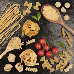 Overhead square photo of different types of pasta on black