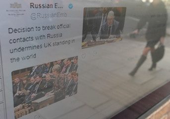 A pedestrian is reflected in a digital screen displaying social media messages from the Russian embassy on a wall outside of the consular section of the embassy in London