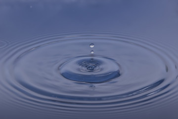 drop of water liquid with splash isolated. the drop explodes in the water sending spray to the sides and circle ripples around it. the water is blue