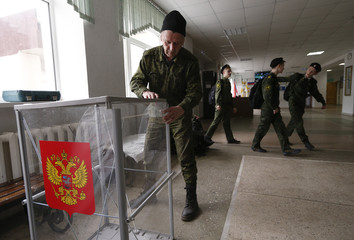 A worker assembles ballot boxes at a polling station ahead of the upcoming presidential election in Stavropol