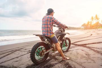 Biker man with his sport motorbike on ocean beach.