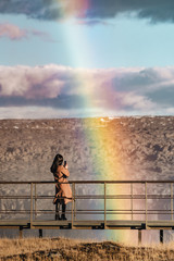 Brunette girl stands in front of a big rainbow taking picture of it