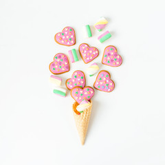 Food composition with gingerbread cookies and marshmallow in waffle cone on white background. Flat lay. top view.