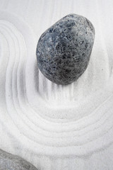 Zen garden stone with curves on sand