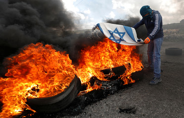 Palestinian demonstrator burns Israeli flag during clashes at a protest against Trump's decision on Jerusalem, near Ramallah, in the occupied West Bank