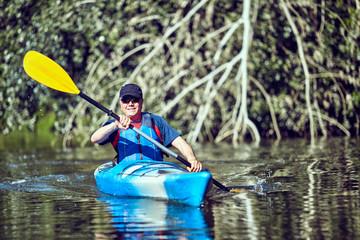 Man paddling a kayak on summer day.