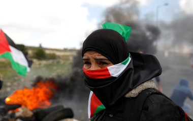 Demonstrator covers his face with a Palestinian flag during clashes with Israeli troops at a protest against Trump's decision on Jerusalem, near Ramallah, in the occupied West Bank