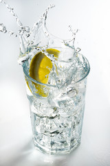 Lemon splashing on a glass against a white background