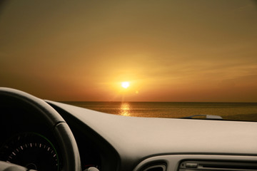 Dark car Interior - steering wheel, shift lever and dashboard. Car modern inside. Front view on sunset and sea background. The sun shines in the glass. glare
