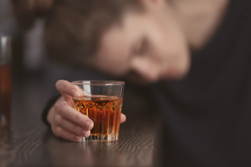 Unconscious drunk woman with glass of drink in bar, closeup. Alcoholism problem