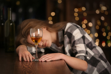 Unconscious drunk woman with glass of wine in bar. Alcoholism problem