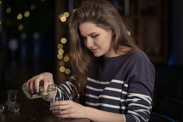 Young woman pouring drink into glass at bar. Alcoholism problem