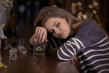 Young woman with bottle of drink in bar. Alcoholism problem
