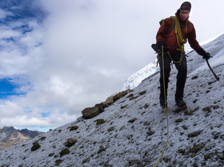 male mountain climber descending a steep snow and scree slope in the Cordillera Blanca in Peru on his way to base camp after submitting a high peak