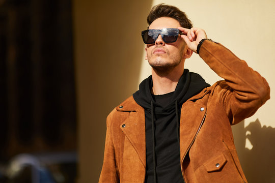 Model looking man stand near the wall and hold his glasses towards the sun shine