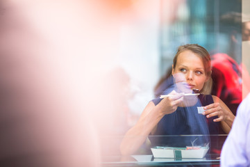 Pretty, young woman eating sushi in a restaurant, having her lunch break, enjoying the food, pausing for a while from her busy corporate/office life (color toned image)