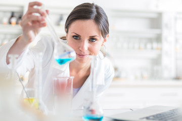 Young, female researcher carrying out experiments in a lab (shallow DOF; color toned image)