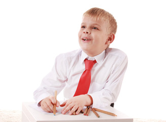 Handsome schoolboy is looking at camera and leaning on the table while drawing