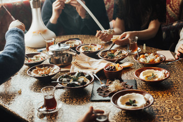 Lebanon cuisine served in restaurant. A young company of people is smoking a hookah and communicating in an oriental restaurant. Traditional meze lunch