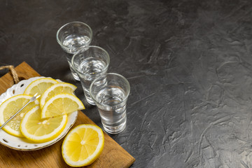 Glass of vodka. And lemon slicing on a plate. Place for your text.