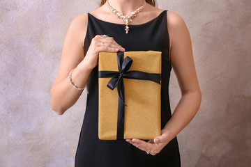 Young woman holding gift box on light background