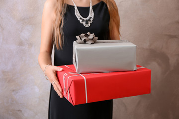 Young woman holding gift boxes on color background