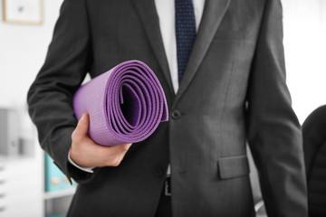 Young businessman holding yoga mat in office, closeup