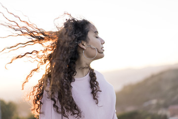 Young woman with blowing hair at evening twilight