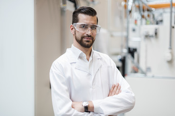 Portrait of man wearing lab coat and safety goggles in factory Wall mural