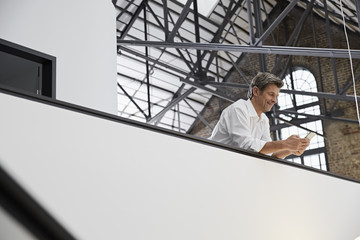 Germany, North-Rhine-Westphalia, Cologne, portrait of mature businessman using smart phone in modern office