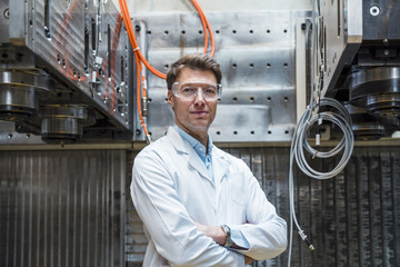 Portrait of man wearing lab coat and safety goggles at machine