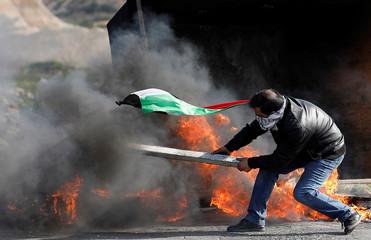 Palestinian demonstrator moves a burning tire during clashes with Israeli troops at a protest against Trump's decision on Jerusalem, near Ramallah, in the occupied West Bank