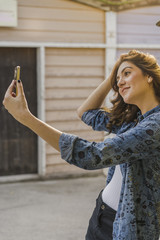 Smiling young woman taking selfie with cell phone