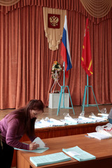 An electoral official receives and counts ballots ahead of the upcoming presidential election in Khislavichi