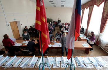 Electoral officials receive and count ballots ahead of the upcoming presidential election in Khislavichi