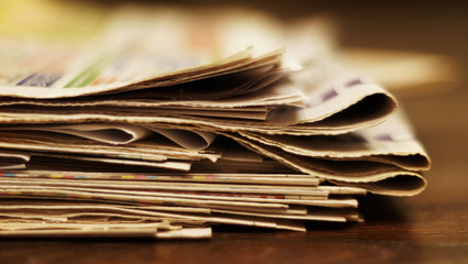Newspapers folded and stacked in a pile, close up