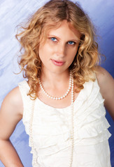 Beautiful blue-eyed curly blonde in front of blue background.