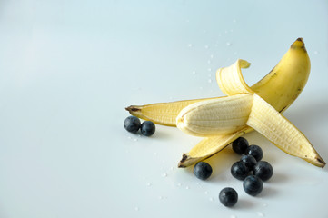 Peeling Ripe Banana with Blueberries on White Background