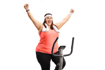 Overweight woman working out on an exercise bicycle and gesturing happiness